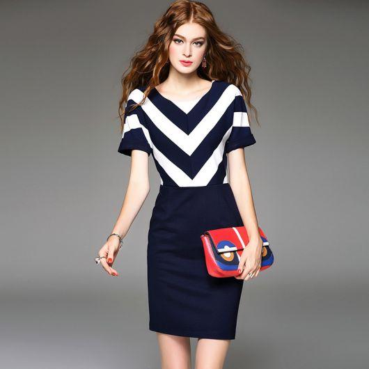 Modelo usa vestido listrado em azul e branco no busto e saia em rom de azul, com bolsa carteira vermelha.