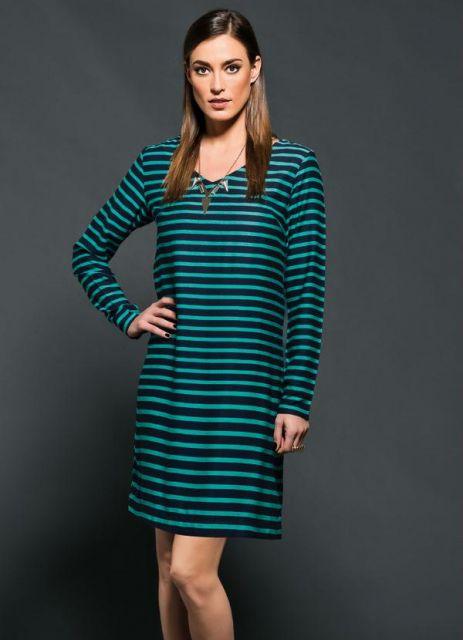 Modelo veste vestido listrado nas cores verde claro e preto.