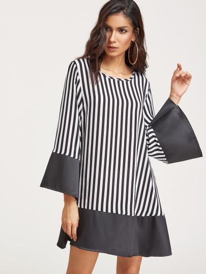 Modelo com vestido preto e branco, listras finas verticais.