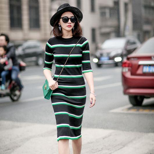 Look com vestido preto de listras verdes e bolsa no mesmo tom.