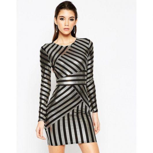 Modelo usa vestido cinza metalizado com listras, diagonais e horizontais nas cores preto.