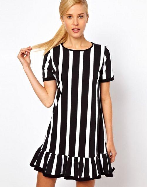 Modelo usa vestido reto com babado na barra, nos tons de preto com branco.