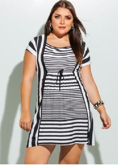 Modelo plus size com vestido listrado em preto e branco.