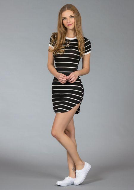 Modelo usa vestido preto curto com laterais com fenda e tenis branco.