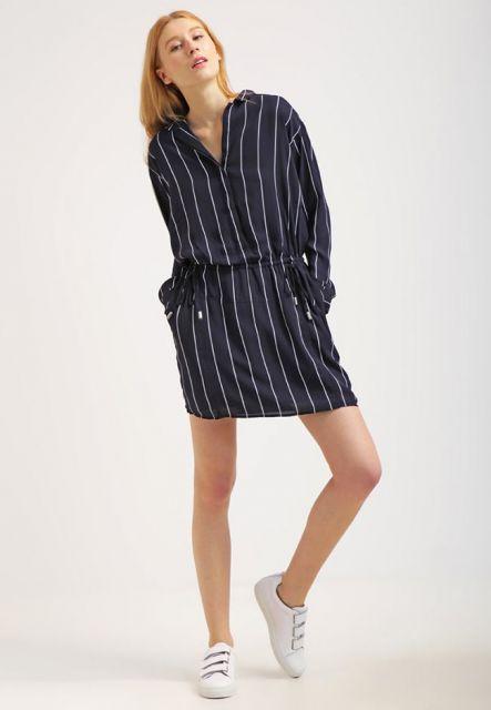 Modelo usa vestido camisa em tom de azul com risca giz em listras brancas.