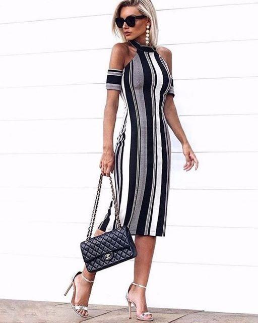 Modelo com vestido de listras nas cores preo, cinza, branco, sandalia cinza prateada e bolsa de mão.