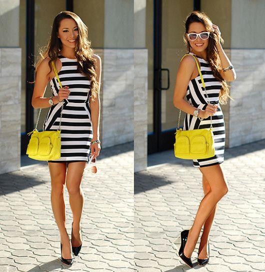 Modelo usa vestido curo em preto e branco, bolsa amarela e sapato scarpin preto.