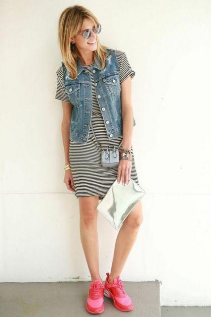 modelo usa vestido preto com listras brancas, colete jeans, bolsa prata, tenis vermelho.