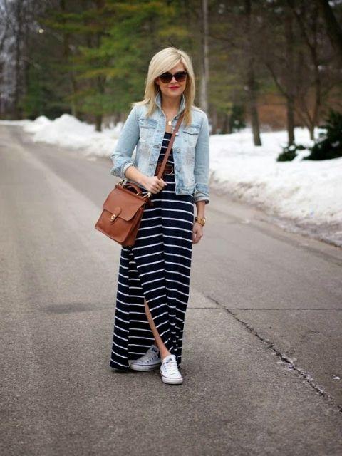 Modelo com vestido longo azul e branco, com fenda, tenis branco, camisa jeans e bolsa transversal em tons terrosos avermelhados.