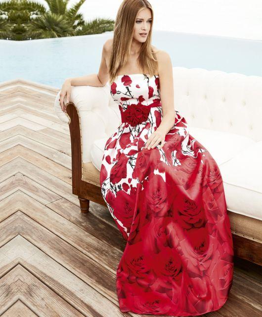 Modelo sentada com vestido nas cores de veremeho e branco estampado.