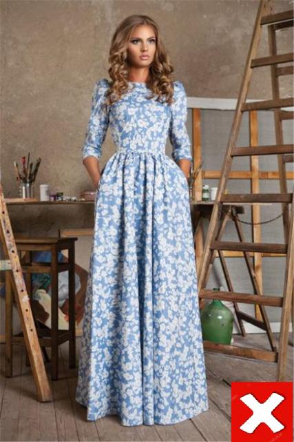 modelo usa vestido azul com estampa, meia manga ´plissado sem decote.