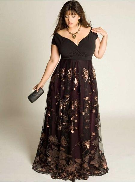 Modelo usa vestido longo com decote V na cor preta, ombro a ombro e detalhes em renda bordada na saia.