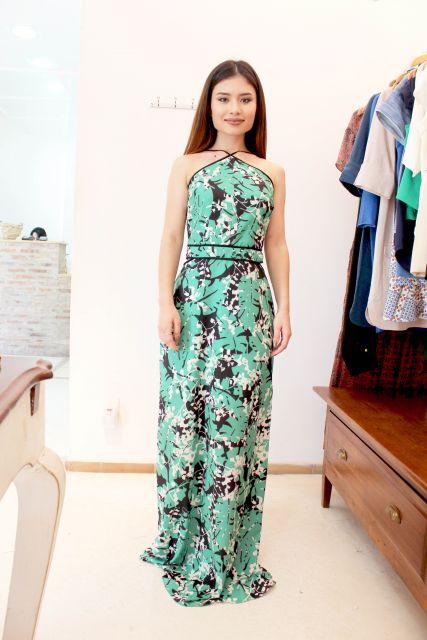 Modelo usa vestido verde, com estampa preto e branco.