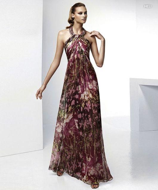 Modelo usa vestido vermelho vinho com estampa esbranquiçada.