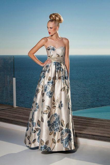 Modelo usa vestido godê, tomara que caia floral em tons de bege com flores azuis.