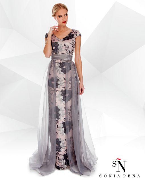 Modelo usa vestido cinza claro com flores azuais marinho, detalhe em voal nas laterais.