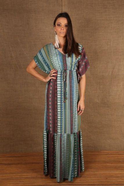 Modelo usa vestido, manga kimono, corte reto estampado em tons de azul e roxo escuro.