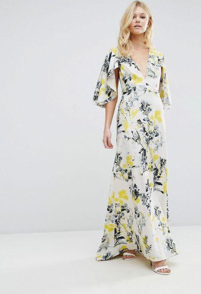 Modelo usa vestido estampadao, cor branca com estyampa de flores amarelas e cinzas, com sandalia branca nudist.