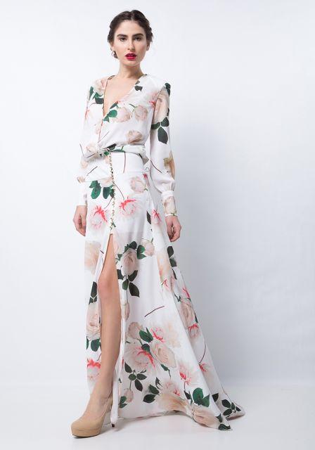 Modelo usa vestido branco,verde com rosa e sapato de salto.