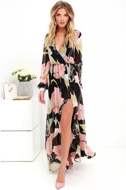 Modelo veste vestido manga longa preto com flores rosa, fenda e decote profundo, com manga longa soltinha.