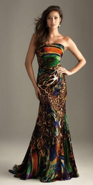 Modelo usa vestido tomara que caia, modelo sereia nos tons de estampado verde, bege e vermelho terra.