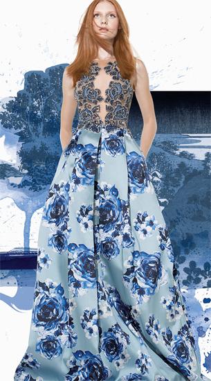 Modelo usa vestido azul estampado, com busto em renda e tule , modelo godê.