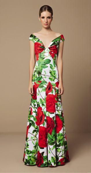 Modelo usa vestido floral branco, com flores em tons de verde e vermelho.