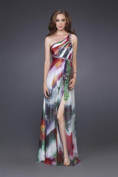 Modelo usa vestido com estampa tinta tie dye em tons de branco, verde, vermelho, de um ombro só.