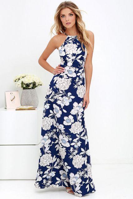 Modelo usa vestido azul com florais em tom de branco.