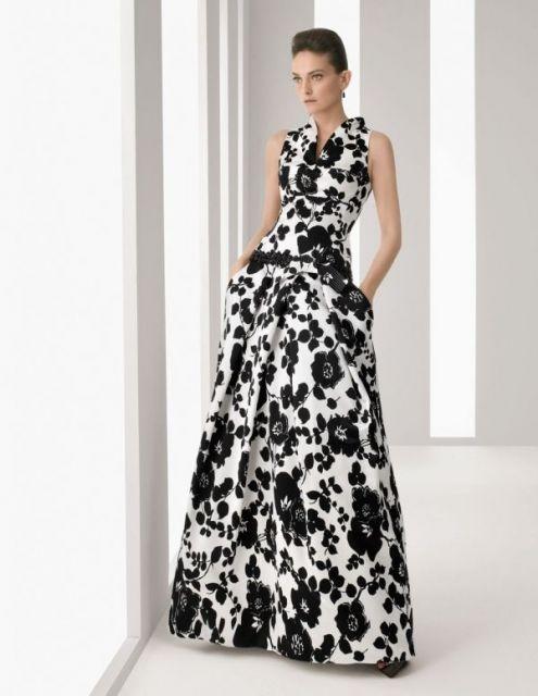 Modelo usa vestido longo floral nas cores de branco ao fundo e flores pretas.