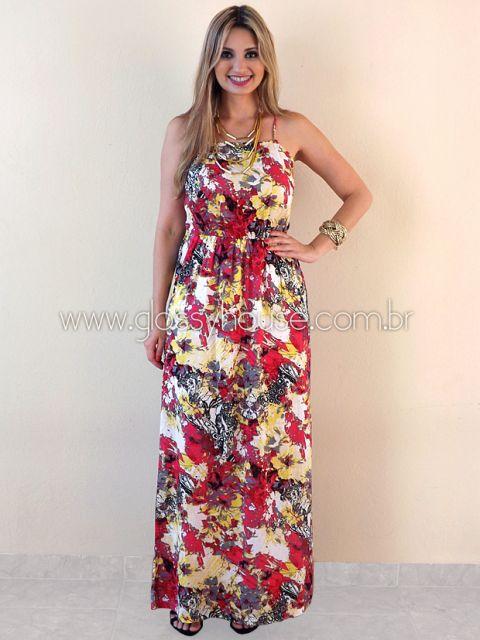 Modelo usa vestido floral graúdo no tom vermelho com branco e amarelo.