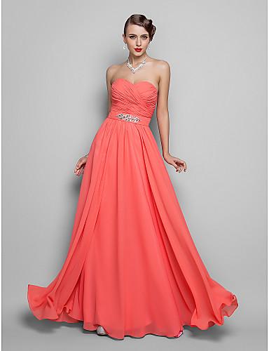 Modelo veste vestido tomara que caia, bufante em tom coral com colar de brilhantes.