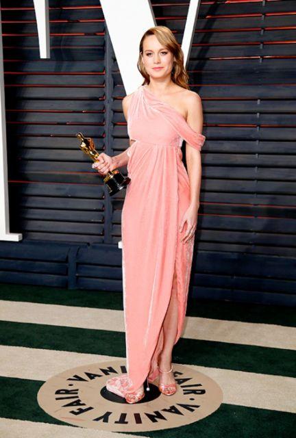 Modelo veste vestido salmão rosê, com detalhe de fenda.