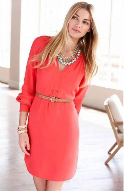 Modelo veste vestido coral, de mangas compridas, decote em v, sutil, cinto bege, colares e pulseiras.