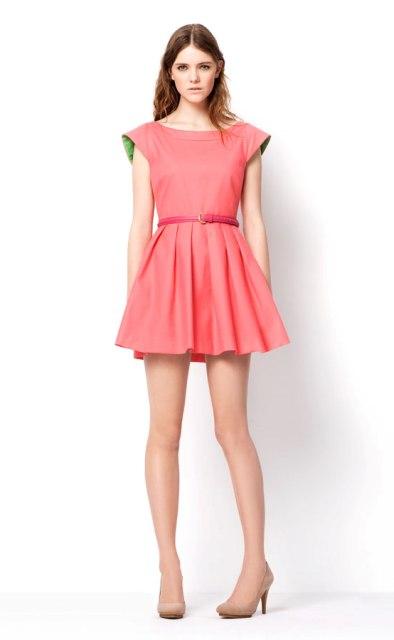 Modelo veste vestido rosa salmao, gode de mangas com sapato de salto.