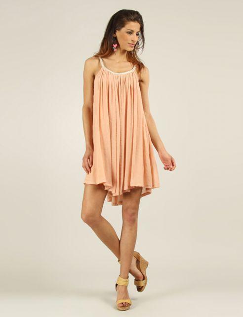 Modelo veste vestido pregadinho, tom salmão nude, com sandália amarela.