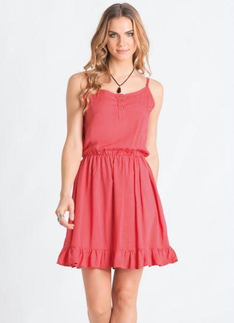 Modelo veste vestido de alcinha curto com barra de babados e tom coral.