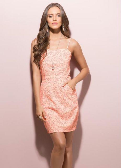 Modelo usa vestido de alcinha com bolsos, tom rosa clarinho salmão.