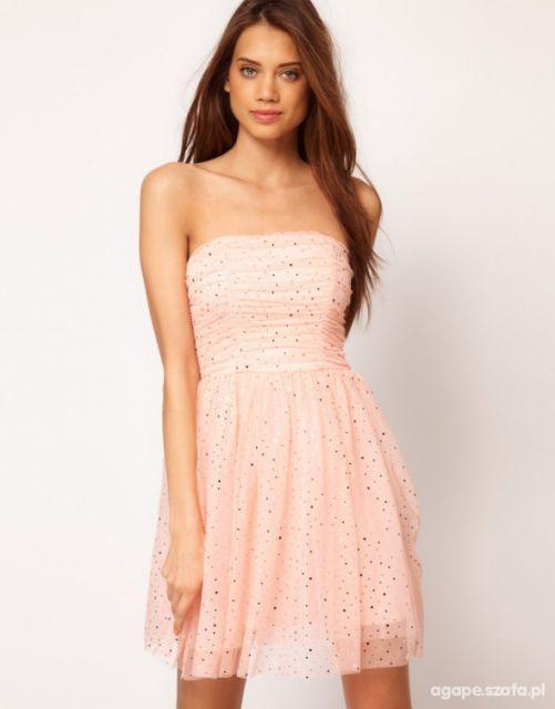 Modelo veste vestido tomara que caia, com detalhe de saia voal, modelo curtinho.