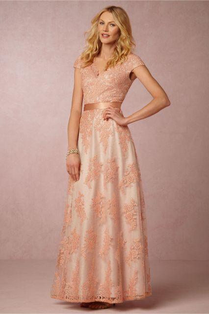 Modelo usa vestido salmão claro, com renda , manga curta.