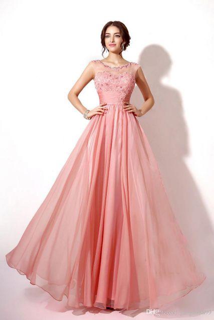 Modelo usa vestido rosê salmão, manga regata, bufante.