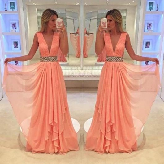 Modelo de vestido longo com detalhe voal, cor salmao, com detalhe na cintura em pedrarias.