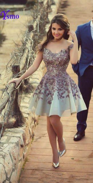 Modelo veste vestido azul claro com bordado roxinho e sapato scarpin dourado.