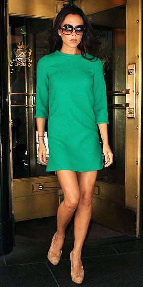 Vitória Beckham veste vestido verde reto e sapato em tom nude e óculos escuros.