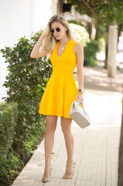Modelo veste vestido amarelo, bolsa de mão e sandália nude.