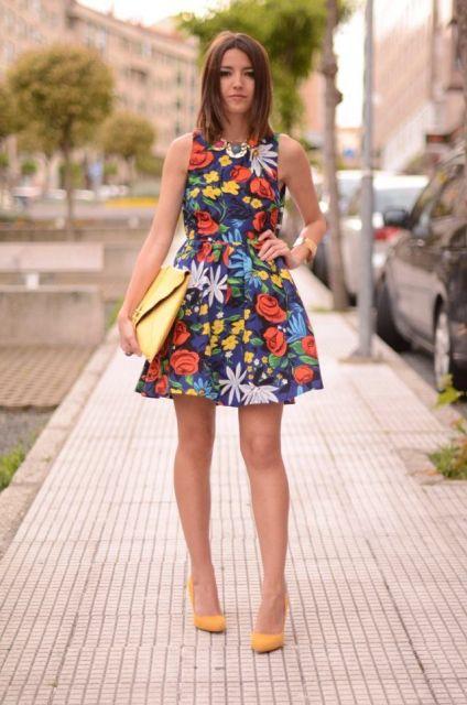 Look com vestido estampado em tons de azul, vermelho, amarelo e branco, bolsa amarela e sapato na mesma cor.