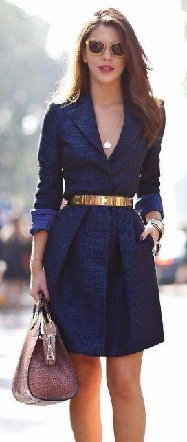 Modelo veste vestido azul marinho, com cinto e bolsa de mão