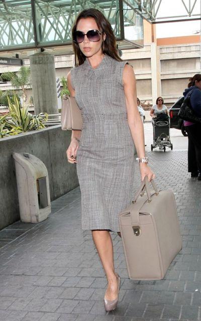 Vitória Beckham veste vestido todo cinza, óculos escuros e bolsa e sapato nude.