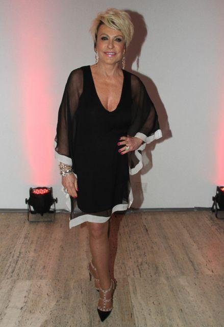 Ana Maria Braga veste vestido preto voal com detalhes em branco, com scarpin preto.