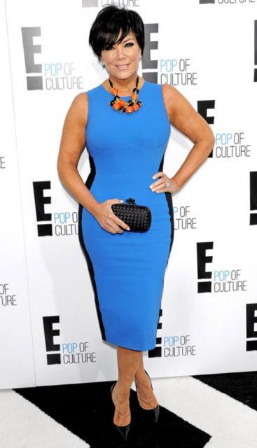 Kris Jenner veste vestido azul com detalhe preto nas laterais e sapato preto e bolsa de mão pequena.
